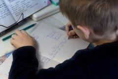 Jongen die met potlood Engelse woorden met de hand op traditioneel wit blocnotedocument schrijven Royalty-vrije Stock Foto's
