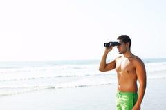 Jongen die met verrekijkers de kust bekijkt royalty-vrije stock foto's