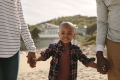 Jongen die met zijn ouders op strand lopen stock afbeeldingen