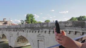 Jongen die mobiele foto van Tiberius-brugoriëntatiepunt Rimini maken Italië stock video