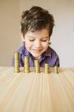 Jongen die muntstukken op een lijst bekijken Stock Foto
