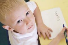 Jongen die naam in primaire klasse leert te schrijven royalty-vrije stock afbeelding