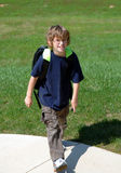 Jongen die naar huis van school loopt Stock Foto's