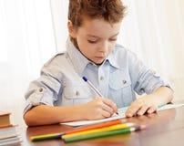 Jongen die in notitieboekje schrijft Stock Afbeeldingen