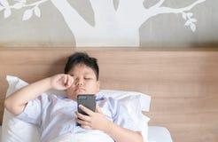 Jongen die ogen na spelsmartphone wrijven stock fotografie