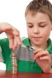 Jongen die omhoog muntstukken stapelt die op wit worden geïsoleerdr Stock Fotografie