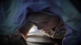 Jongen die onder algemeen en het letten op beeldverhaal op aanrakingsstootkussen liggen stock video