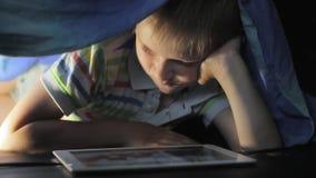 Jongen die onder algemeen en het letten op beeldverhaal op aanrakingsstootkussen liggen stock videobeelden