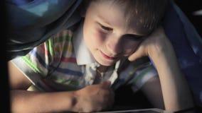 Jongen die onder algemeen en het letten op beeldverhaal op aanrakingsstootkussen liggen stock footage