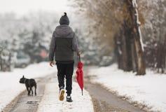 Jongen die onderaan de sneeuwstraat lopen stock foto's