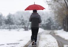 Jongen die onderaan de sneeuwstraat lopen stock foto