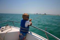 Jongen die op boot vist Stock Foto