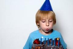 Jongen die op de kaarsen blaast die in de cake worden geplaatst Royalty-vrije Stock Foto