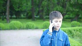 Jongen die op de telefoon, openluchtschot spreken stock video
