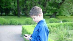 Jongen die op de telefoon, openluchtschot spreken stock videobeelden