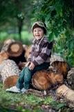 Jongen, die op een boomboomstammen zitten Stock Foto's