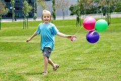 Jongen die op een gras met ballons loopt Stock Foto's
