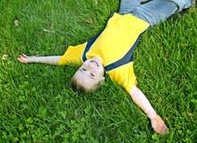 Jongen die op Gras legt Royalty-vrije Stock Afbeeldingen