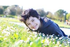 Jongen die op groen gras liggen royalty-vrije stock fotografie