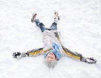 Jongen die op Grond legt die de Engel van de Sneeuw maakt Stock Foto's