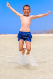 Jongen die op het strand springen Stock Afbeelding
