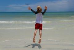 Jongen die op het strand voor oceaangolven springen Royalty-vrije Stock Fotografie