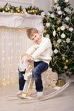 Jongen die op Kerstmis van het paardnieuwjaar slingeren Royalty-vrije Stock Foto