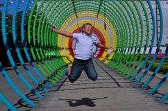 Jongen die op regenboogachtergrond springen Royalty-vrije Stock Fotografie
