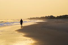 Jongen die op strand bij zonsondergang loopt Royalty-vrije Stock Afbeeldingen