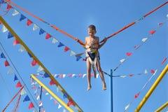Jongen die op vermaak springen Stock Foto