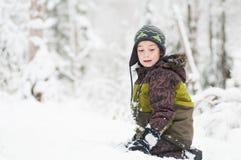Jongen die in openlucht in de sneeuw spelen stock foto's