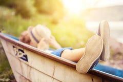 Jongen die in oude boot in het beeld van de meerkust dicht omhoog liggen Royalty-vrije Stock Afbeeldingen