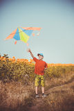 Jongen die over het gebied met vlieger lopen die over zijn hoofd vliegen Royalty-vrije Stock Afbeeldingen