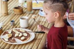 Jongen die pannekoek met banaan en chocolade eten Royalty-vrije Stock Foto's