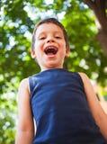 Jongen die in park lachen stock fotografie