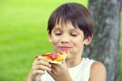Jongen die pizza eet stock fotografie
