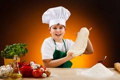 Jongen die pizzadeeg maakt Stock Afbeeldingen