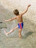Jongen die plons in het water maakt Stock Afbeeldingen
