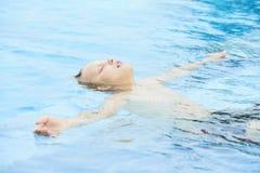 Jongen die in pool rusten stock fotografie