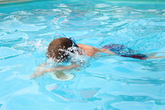 Jongen die in pool zwemmen Stock Afbeeldingen