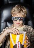 Jongen die Popcorn eten terwijl het Letten van op 3D Film Royalty-vrije Stock Foto