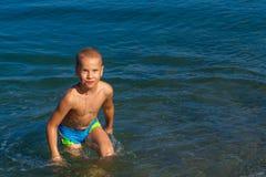 Jongen die pret hebben en in het overzees zwemmen stock afbeeldingen