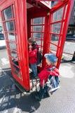 Jongen die in publieke telefoonceldoos spreekt royalty-vrije stock foto's