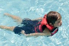 Jongen die in reddingsvest zwemt stock fotografie