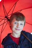 Jongen die rode paraplu houdt Stock Foto's
