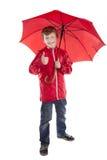 Jongen die rode paraplu over witte achtergrond houdt Royalty-vrije Stock Fotografie