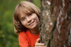 Jongen die in rode T-shirt uit van achter een boomboomstam gluurt Stock Fotografie