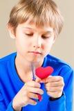 Jongen die rood document hart met schaar snijden stock afbeeldingen