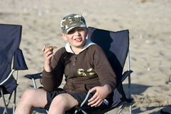 Jongen die sandwich op strand eet Stock Foto's
