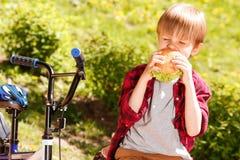 Jongen die sandwich in park afbijten stock fotografie